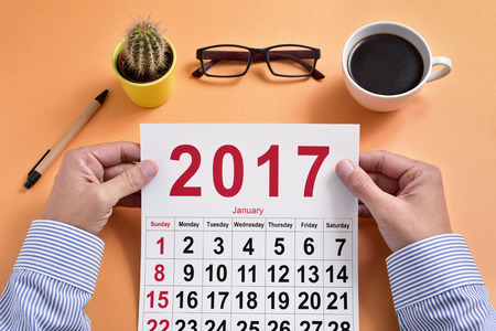 headman: a young caucasian businessman observes a 2017 calendar sitting at his office desk, where there is a pen, a cactus, a pair of eyeglasses and a cup of coffee