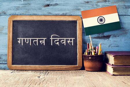 devanagari: a chalkboard with the text Republic Day written in Hindi and a flag of India, on a rustic wooden surface, against a blue wooden background Stock Photo