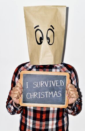 grouch: a young caucasian man dressing casual wear with a paper bag in his head shows a chalkboard with the text I survived christmas written in it