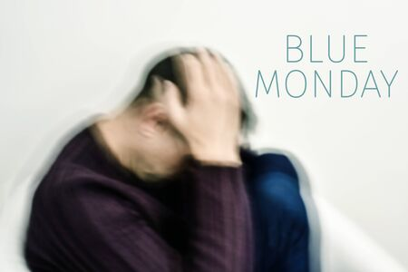 closeup of a blurred young caucasian man curled up with his hands in his head and the text blue monday Stock Photo