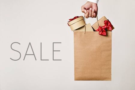 rebates: closeup of the hand of a young caucasian man holding a paper shopping bag full of gifts and the word sale Stock Photo