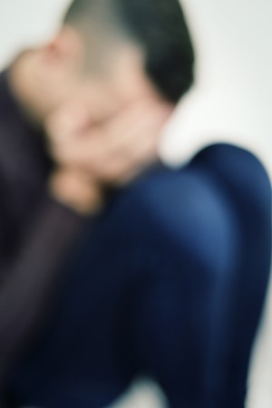 unemployed dismissed: closeup of a blurred young caucasian man curled up with his hands in his face