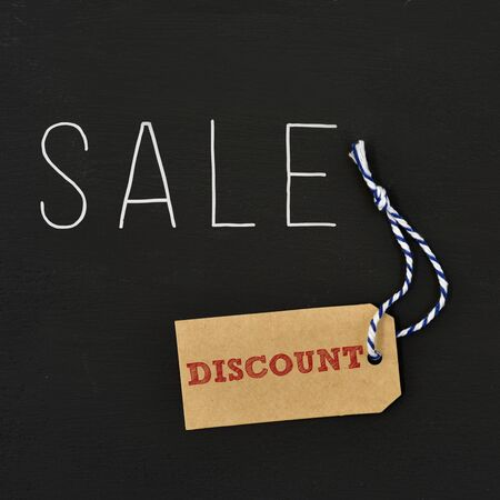 rebates: a brown paper label with the text discount written in it and the word sale written in white on a dark gray background