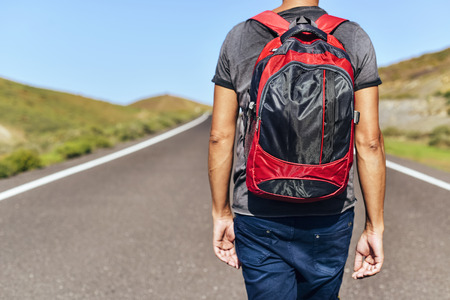 closeup of a young caucasian man seen from behind carrying a backpack walking by a minor road Stock Photo
