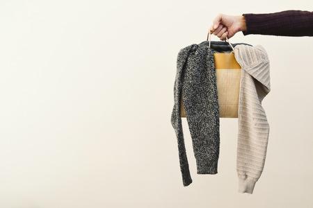 compras compulsivas: primer plano de la mano de un hombre caucásico joven con una bolsa de papel llena de ropa y un espacio negativo a la izquierda Foto de archivo