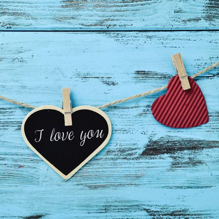 a heart-shaped signboard with the text I love you and a red heart hung with clothespins in a clothes line, against a blue rustic wooden background