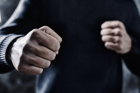 closeup of a young caucasian man in casual wear with a threatening gesture, ready to punch or fight with his fists