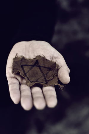 captives: closeup of a ragged Jewish badge in the palm of a young man