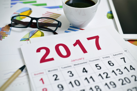 headman: closeup of a 2017 calendar, a pair of eyeglasses, a cup of coffee and a tablet computer on an office desk full of charts