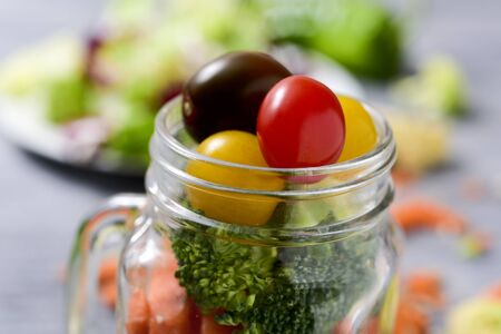cornsalad: closeup of a salad with a mix of different lettuces, broccoli, green pepper, carrot and cherry tomatoes of different colors served in a mason jar, on a gray rustic wooden table Stock Photo