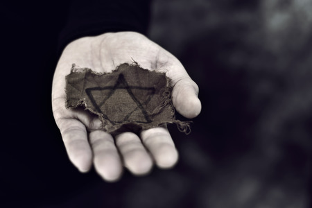 closeup of a ragged Jewish badge in the palm of a young man