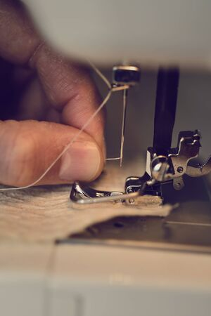 exploited: closeup of a young man threading the needle of a sewing machine