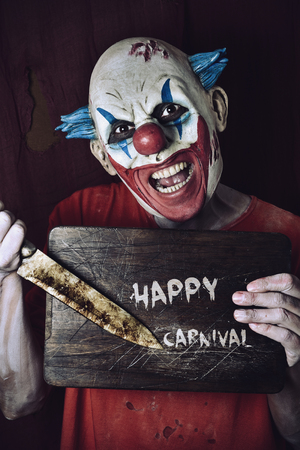 the scars: a scary evil clown pointing a big knife at a wore chopping board with the text happy carnival written in it Stock Photo