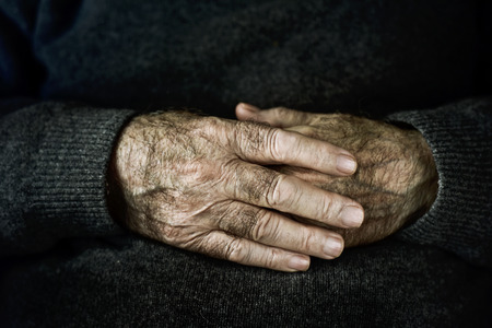 old hand: closeup of the wrinkled hands of an old caucasian man, wearing a dark gray sweater Stock Photo