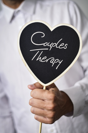 systemic: a young caucasian man wearing a white shirt shows a heart-shaped signboard with the text couples therapy written in it
