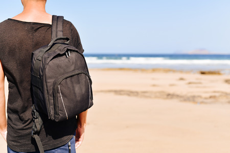 itinerant: closeup of a young caucasian man seen from behind wearing a t-shirt and carrying a backpack, standing on a white sand beach