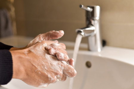 closeup of a young caucasian man washing his hands with soap in the sink of a bathroom