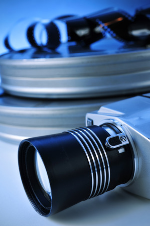 filmmaker: closeup of a retro film camera, some film strips and some metal movie film reel canisters on a table with, a blue toning