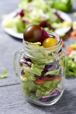 cornsalad: a salad with a mix of different lettuces, broccoli, green pepper, carrot and cherry tomatoes of different colors served in a mason jar, on a gray rustic wooden table