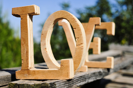 some three-dimensional wooden letters forming the word love, placed on a weathered wooden surface outdoors, with trees in the background Stock Photo
