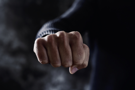 attacker: closeup of a young caucasian man in casual wear with a threatening gesture, with his fist clenched and pointing to the observer Stock Photo