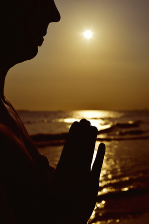 yogi aura: the silhouette of a young man with his hands put together as prying in front of the sea in backlight