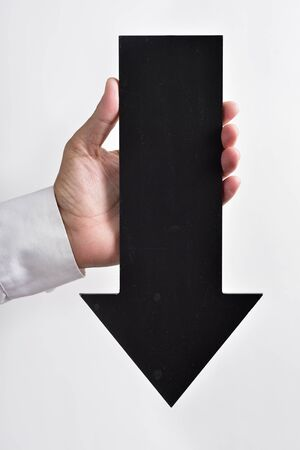 downwards: closeup of a young caucasian man holding a black arrow-shaped signboard pointing downwards Stock Photo