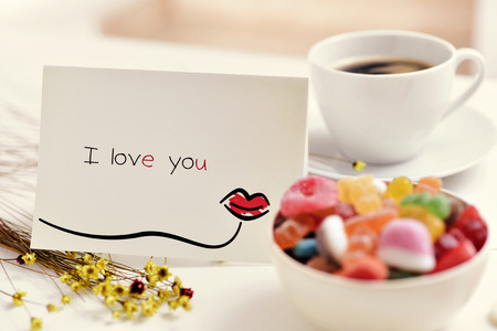 a homemade postcard, made by myself, with a kiss drawn in it and the text I love you, on a white table next to a cup of coffee, some flowers and a bowl with candies