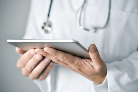 closeup of a young caucasian doctor man wearing a white coat using a tablet computer 스톡 콘텐츠