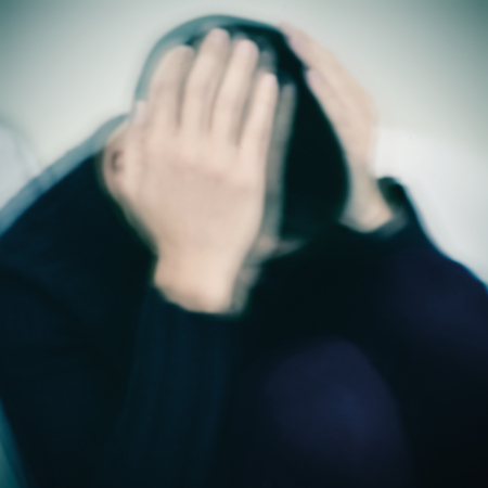 closeup of a young caucasian man curled up with his hands in his face, with a strong blur processing to create a dramatic effect Stock Photo