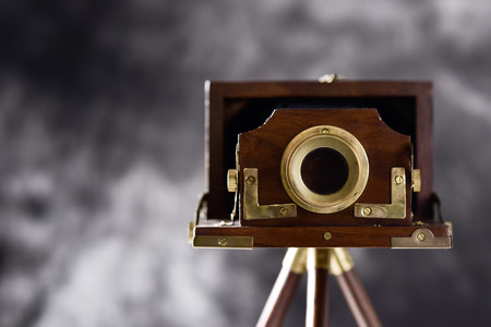 an old wooden folding camera in a wooden tripod, against a gradient gray background