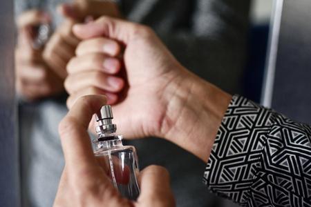 closeup of a young caucasian man spraying perfume on his wrists Archivio Fotografico