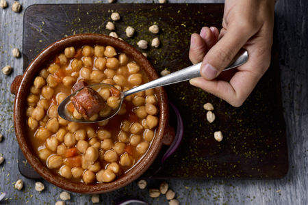 garbanzo bean: high-angle shot of the hand of a man with a spoon and an earthenware bowl with spanish cocido madrileno, a stew typical of madrid with chickpeas, pork, bacon, chorizo and ham, on a rustic wooden table