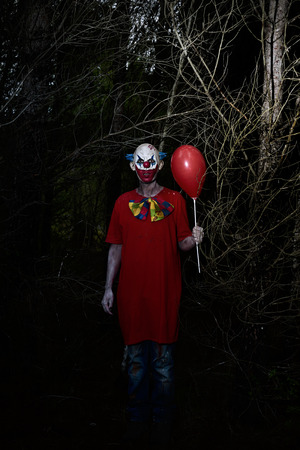 a scary evil clown wearing a dirty costume, holding a red balloon in his hand, in the woods at night