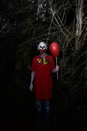 Een enge kwade clown het dragen van een vuile kostuum, met een rode ballon in de hand, in het bos 's nachts Stockfoto - 71131893