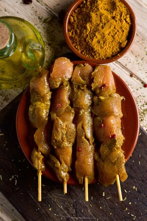 skewed: closeup of some raw spiced chicken meat skewers in an earthenware plate, on a rustic wooden table, next to a glass cruet with olive oil and a bowl with curry powder Stock Photo