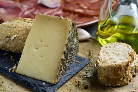 Nahaufnahme eines Stückes Manchego-Käse, einige Scheiben Brot, eine Menage mit Olivenöl und ein Teller mit einer Auswahl an verschiedenen spanischen Wurstwaren wie Chorizo, Schweinefilet und Serrano-Schinken