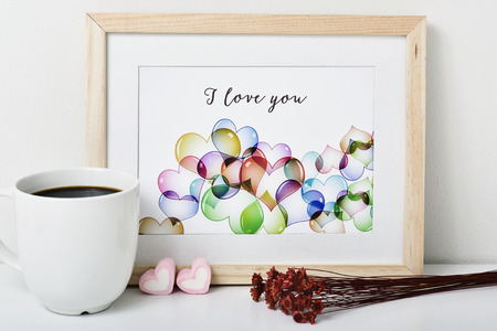 dry flowers: a wooden-framed picture with an illustration, made by myself, with some hearts and the text I love you, a cup of coffee, some heart-shaped marshmallows and a bunch of dry flowers on a white surface