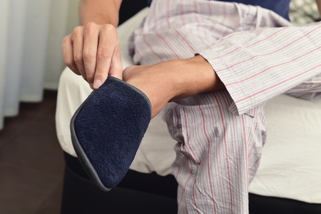 houseshoe: closeup of a young caucasian man in pajamas sitting on the edge of the bed putting on or off a pair of warm slippers Stock Photo