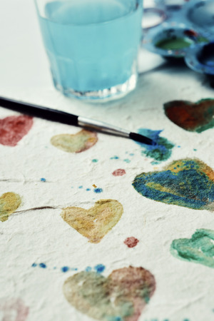 do it yourself: closeup of a piece of paper with some hearts of different colors painted with watercolor paint Stock Photo