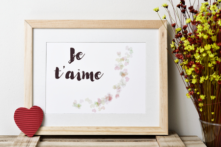 dry flowers: a wooden-framed picture with an illustration, made by myself, with some hearts and the text je t aime, I love you, written in french, a red heart and a bunch of dry flowers on a wooden surface