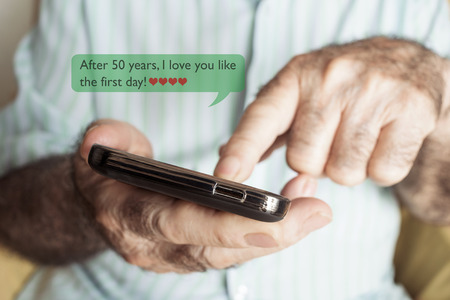 closeup of an old caucasian man sending or reading a text message in his smartphone with the text after 50 years I love you like the first day Banco de Imagens