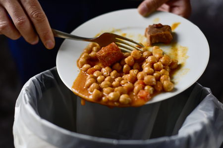 étel: vértes egy fiatal, kaukázusi, ember dobott a maradék egy tányér pörkölt csicseriborsó kukába Stock fotó