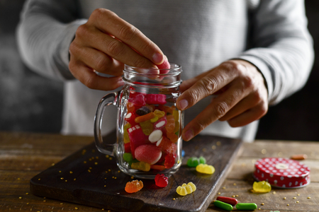 closeup of a young caucasian man introducing candies with different flavors and colors into a mason jar, on a rustic wooden table