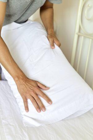 soltería: joven introducción de una almohada en una funda de almohada mientras se está haciendo la cama Foto de archivo