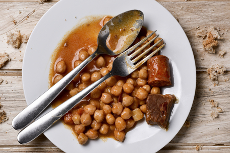 surfeit: high-angle shot of a plate with remains of chickpea stew and remains of bread, on a white rustic wooden table