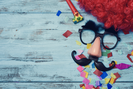 a red wig, a pair of fake black glasses with eyebrows, a nose and a mustache forming the face of a man on a blue rustic wooden surface full of confetti, and a blank space on the left