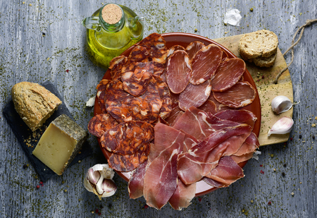cruet: high-angle shot of a plate with an assortment of different spanish cold meats as chorizo, cured pork tenderloin and serrano ham, a piece of manchego cheese, bread and a cruet with olive oil on a table Stock Photo