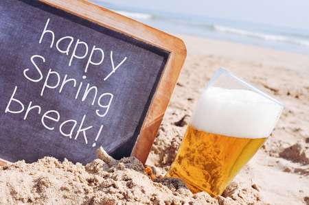 closeup of a wooden-framed chalkboard with the text happy spring break written in it, and a glass of refreshing beer, on the sand of a beach Stock Photo