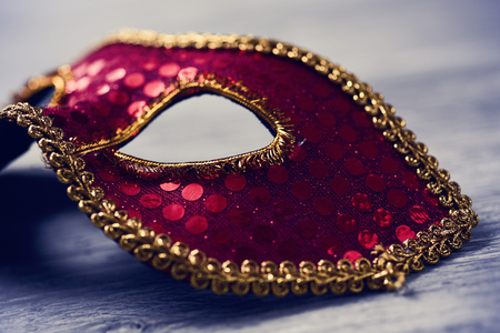 carnevale: closeup of an elegant red and golden carnival mask on a rustic wooden surface Stock Photo